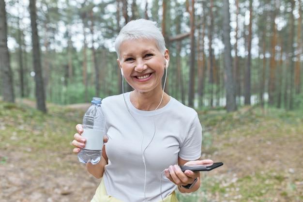 Fröhliche rentnerin, die sich nach dem cardio-training im freien ausruht, im kiefernwald mit handy und flasche wasser posiert, sich erfrischt und musik hört