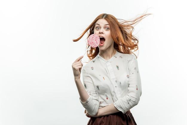 Fröhliche rothaarige frau mit einem lutscher in den händen emotionen öffnen mund süßigkeiten
