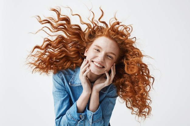 Fröhliche rothaarige frau mit fliegendem lockigem haar, das lachend lächelt.