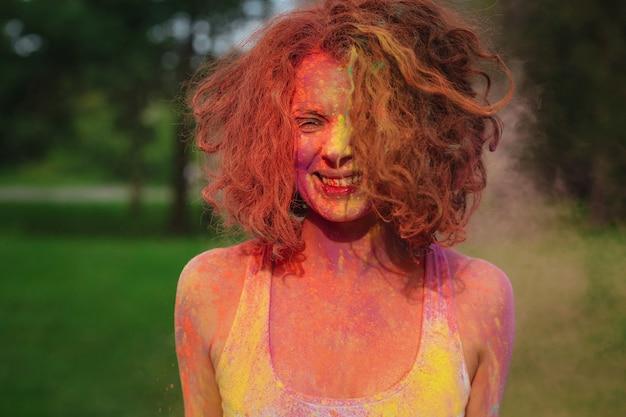 Fröhliche rothaarige frau posiert mit bunter trockener holi-farbe im park bedeckt