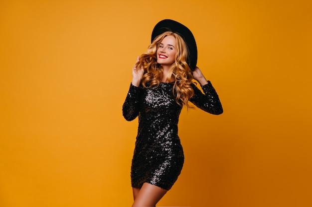 Fröhliche schlanke frau in der partykleidung, die für ereignis vorbereitet. wunderschönes blondes mädchen in hut und schwarzem kleid.