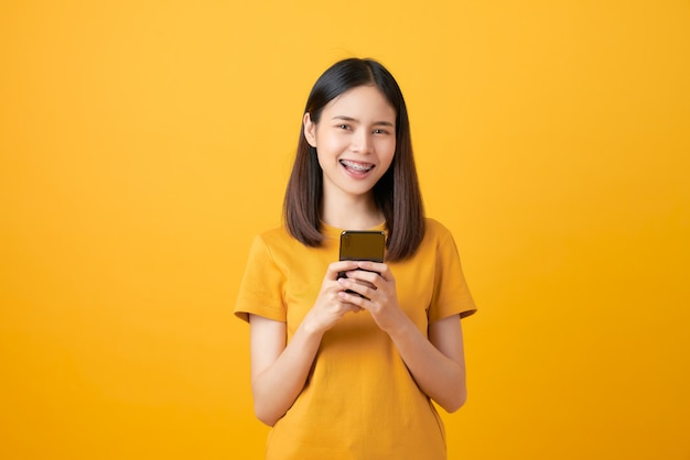 Fröhliche schöne asiatische frau, die ein smartphone hält