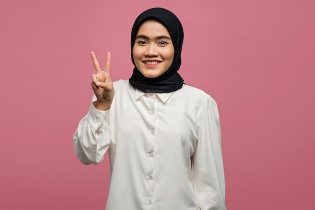 Fröhliche schöne asiatische frau, die ein weißes hemd trägt