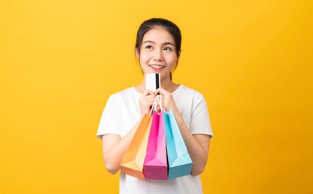 Fröhliche schöne asiatische frau, die mehrfarbige einkaufstaschen und kreditkarte auf orange hintergrund hält.