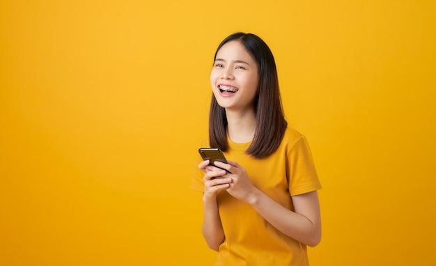 Fröhliche schöne asiatische frau, die smartphone auf hellgelbem hintergrund hält.