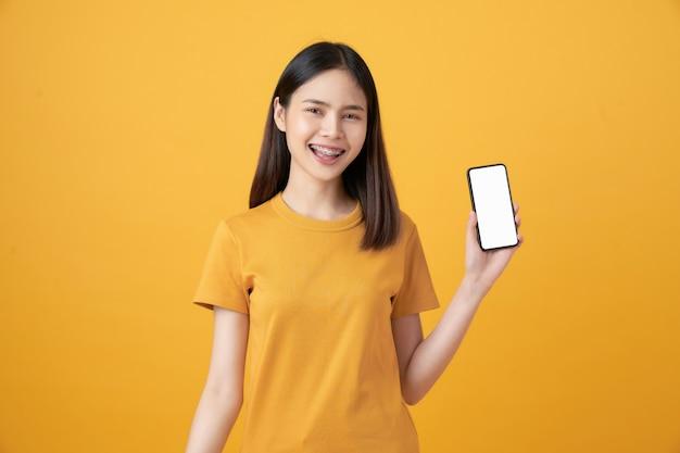 Fröhliche schöne asiatische frau, die smartphone auf hellgelber wand hält