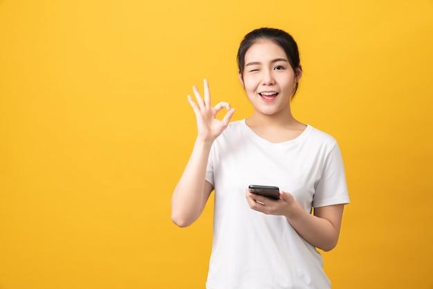Fröhliche schöne asiatische frau, die smartphone hält und ok zeichen auf hellgelbem hintergrund zeigt.