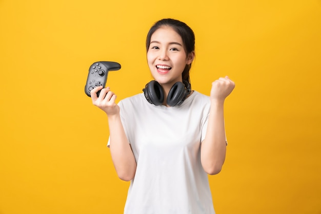 Fröhliche schöne asiatische frau im lässigen gelben t-shirt und beim spielen von videospielen unter verwendung von joysticks mit kopfhörern auf orange hintergrund.