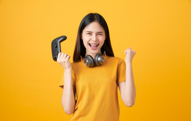 Fröhliche schöne asiatische frau im lässigen gelben t-shirt und beim spielen von videospielen unter verwendung von joysticks mit kopfhörern