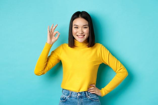 Fröhliche schöne asiatische frau lächelt, zeigt eine gute geste zur zustimmung, sagt ja, steht erfreut über blauem hintergrund.