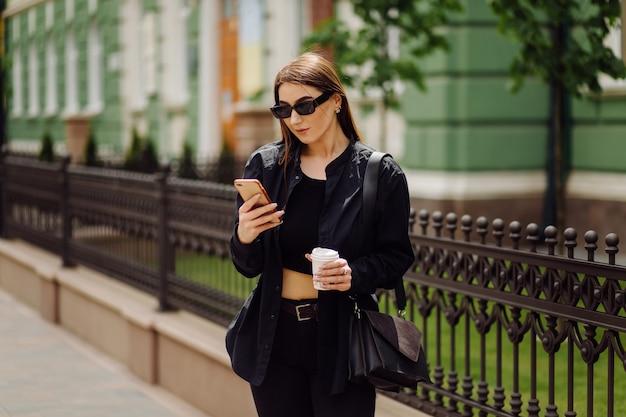 Fröhliche schöne brünette frau in guter laune verwenden telefon außerhalb