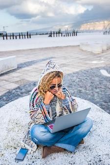 Fröhliche schöne erwachsene frau mit laptop-computer auf dem boden sitzend in der stadt
