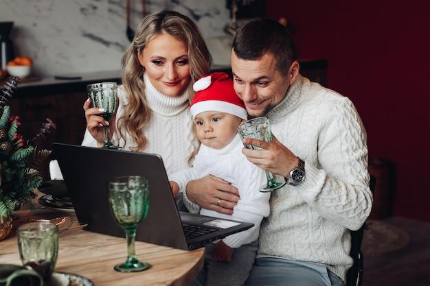 Fröhliche schöne familie mit einem baby, das getränke aufzieht, während sie über laptop von zu hause aus kommuniziert.
