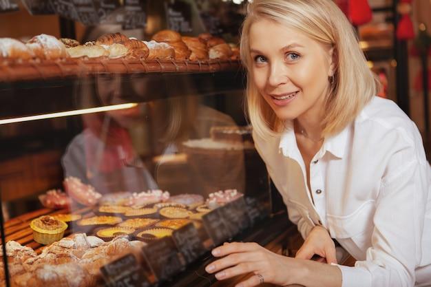 Fröhliche schöne frau, die beim einkaufen für köstliches gebäck am kaffeehaus lächelt.