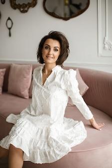 Fröhliche schöne frau, die ein weißes kleid trägt, das auf einem rosa geräumigen sofa sitzt und lächelt. stil und modekonzept