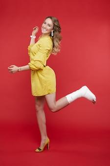 Fröhliche schöne frau im gelben kleid, die spaß mit gips auf ihrem bein hat.