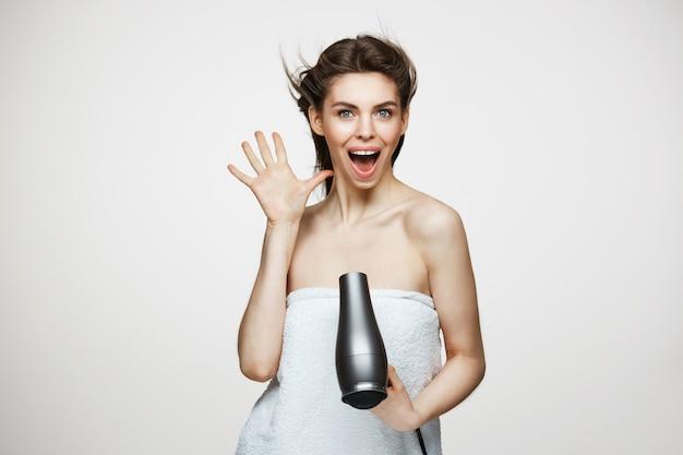 Fröhliche schöne frau im handtuch lächelnd lachend singend mit fön, der lustiges gesicht macht. beauty spa und kosmetologie.