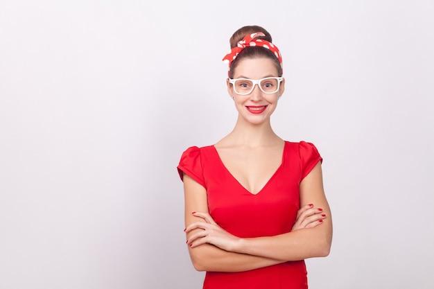 Fröhliche schöne frau in rotem kleid und weißer brille lächelnd