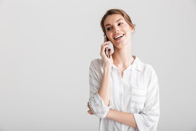 Fröhliche schöne frau lacht und spricht auf dem handy isoliert auf weißem hintergrund