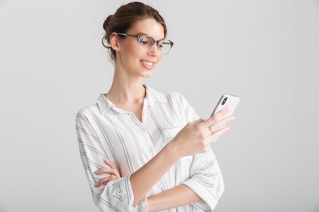 Fröhliche schöne frau mit brille, die auf dem handy auf weißem hintergrund tippt