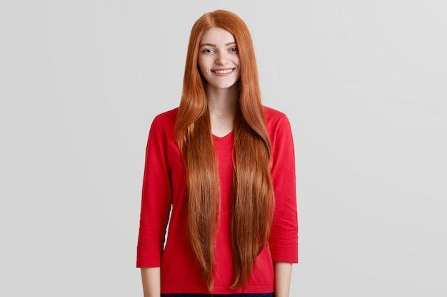 Fröhliche schöne frau mit sehr langen roten haaren, sommersprossigem gesicht, gekleidet in lässigen roten pullover, posiert gegen weiße wand, hat ein angenehm sanftes lächeln. positivität, schönheit und stilkonzept