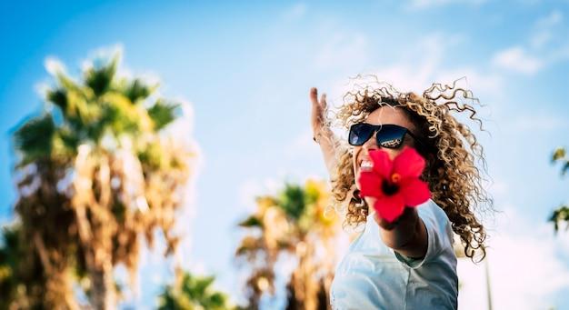 Fröhliche schöne frau mit sonnenbrille mit lockigem haar, die sich aufgeregt fühlt und rote blume mit ausgestreckten armen gegen den himmel hält. fröhliche frau, die spaß hat, frische blumen im freien zu halten