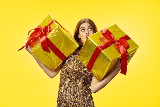 Fröhliche schöne frau mit zwei geschenken in großen kisten