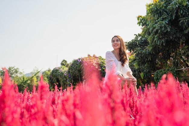 Fröhliche schöne junge asiatische frau sitzt mit erhobenen armen in hahnenkammblume, die im garten blüht