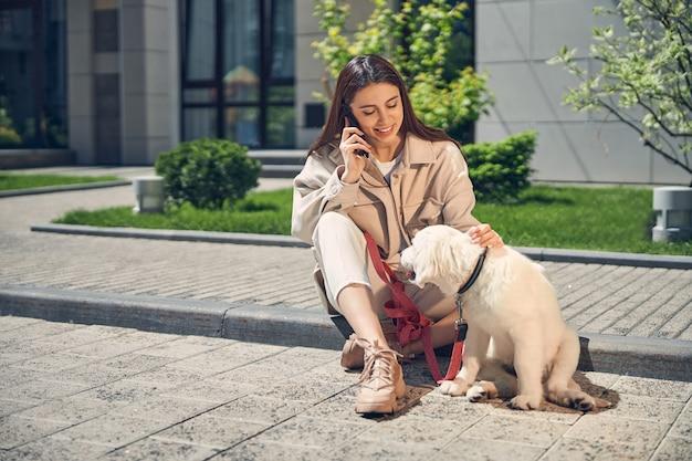 Fröhliche schöne junge dame, die neben ihrem hund am rand des bürgersteigs sitzt