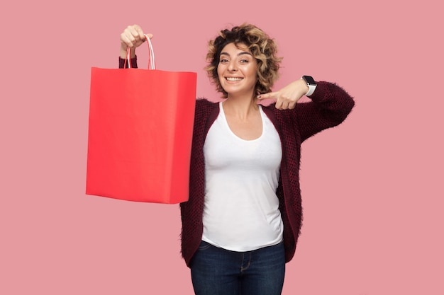 Fröhliche schöne junge frau im blauen hemd mit lockiger frisur, die mit dem finger auf einkaufstüten und ein zahniges lächeln steht und in die kamera schaut. studioaufnahme, rosa hintergrund, isoliert, drinnen