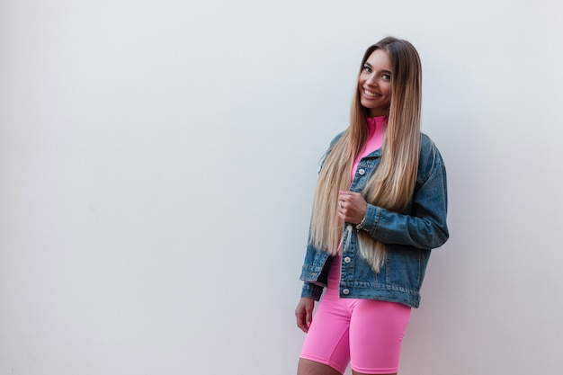 Fröhliche schöne junge frau im trendigen rosa top in rosa shorts in einer jeansjacke mit süßem lächeln entspannt sich in der nähe einer vintage-wand auf der straße. glückliches süßes mädchenmodell im freien. retro-stil.