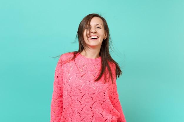 Fröhliche schöne junge frau in gestricktem rosa pullover mit flatternden haaren einzeln auf blauem türkisfarbenem wandhintergrund, studioporträt. menschen aufrichtige emotionen, lifestyle-konzept. kopieren sie platz.