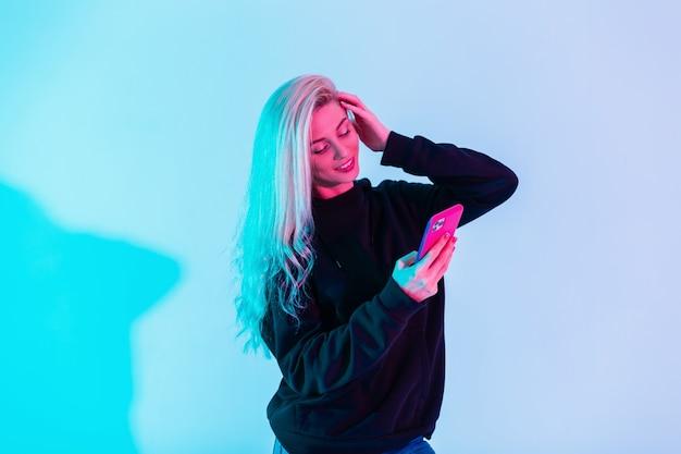Fröhliche schöne junge frau in modischem, lässigem schwarzem sweatshirt mit handy schreibt eine nachricht in sozialen netzwerken auf buntem neonrosa hellem hintergrund im studio