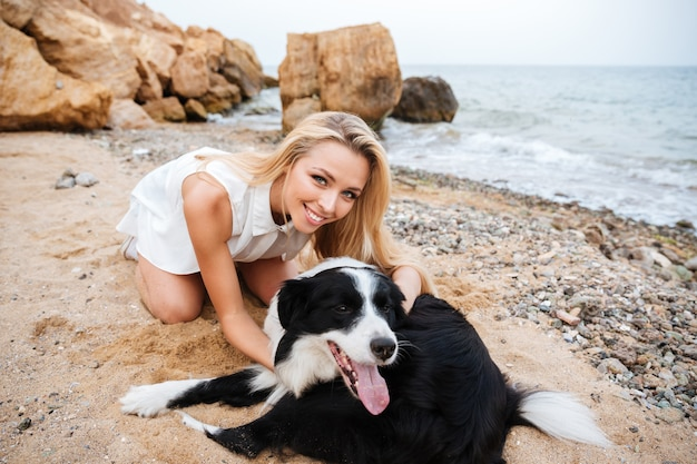Fröhliche schöne junge frau umarmt ihren hund am strand