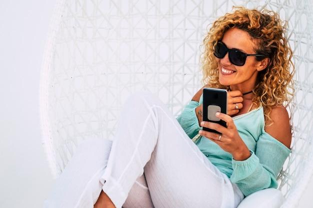 Fröhliche, schöne, lockige junge erwachsene frau, die das handy im freien benutzt, setzen sich auf einen weißen gartenstuhl - lächeln und genießen sie die freizeitaktivität der outdoor-technologie