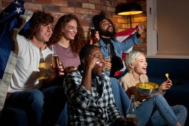 Fröhliche schreiende schreiende studentenfreunde fans, die sich am freien tag ausruhen, popcorn essen und bier trinken, tore feiern oder ihre lieblingsmannschaft gewinnen