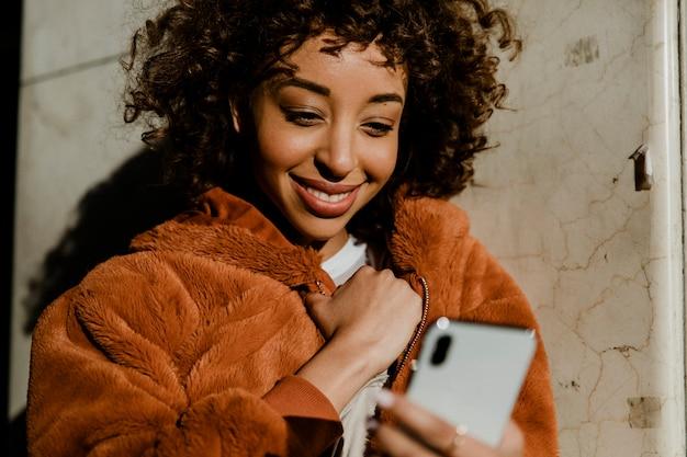 Fröhliche schwarze frau mit ihrem telefon in der innenstadt