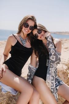 Fröhliche schwestern in denselben schwarzen badeanzügen sitzen zusammen auf dem stein und lächeln auf see. entzückende dunkelhaarige mädchen in sonnenbrillen und halsketten, die an sonnigem tag auf dem resort ruhen