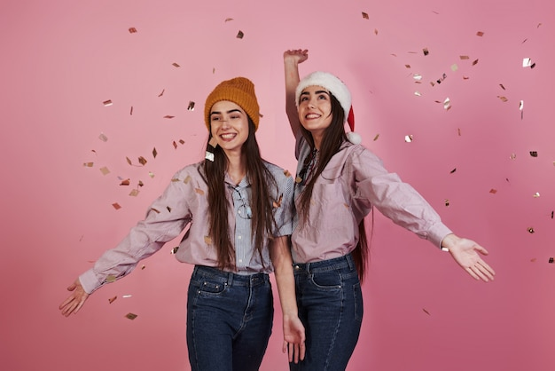 Fröhliche schwestern. neujahrskonzeption. zwei zwillinge spielen und werfen goldenes konfetti in die luft