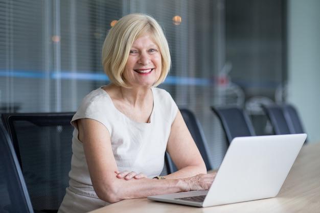 Fröhliche senior geschäftsfrau arbeitet im büro