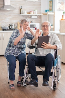 Fröhliche seniorin winkt auf videokonferenz in der küche. behinderter älterer mann im rollstuhl und seine frau bei einer videokonferenz auf dem tablet-pc in der küche. gelähmter alter mann und seine frau haben