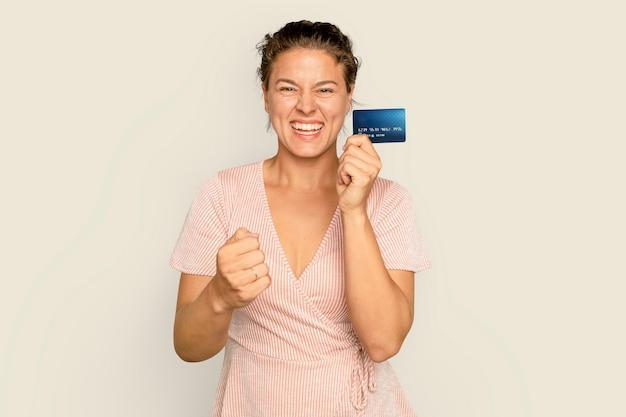 Fröhliche shopaholic-frau, die bargeldlose zahlung mit kreditkarte hält