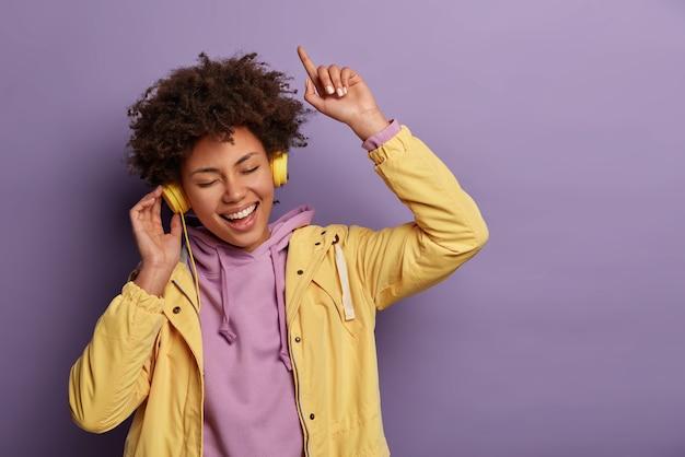Fröhliche sorglose frau genießt musik in neuen kopfhörern