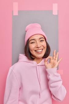 Fröhliche sorglose frau zeigt eine gute geste zur zustimmung zeigt empfehlungsschild stimmt mit ihnen überein lobt gute arbeit trägt hoodie und hut posiert drinnen
