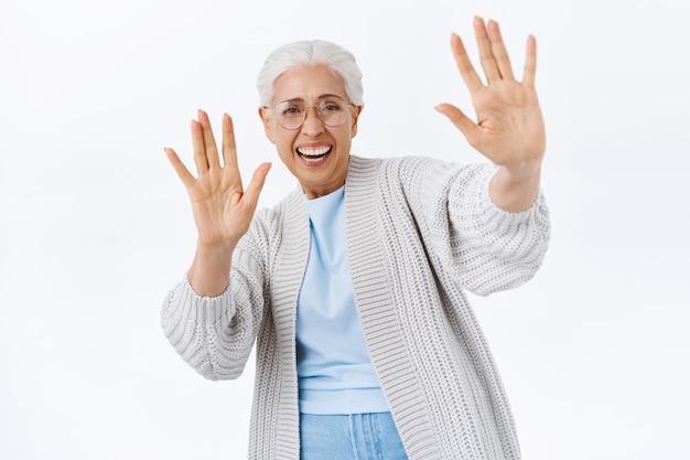 Fröhliche, sorglose, fröhliche seniorin, die mit kindern spielt, sich hingibt oder genug sagt, versucht, aktiv und verspielt herunterzukommen, die hände in stopp- oder okay-geste hebt, lachen