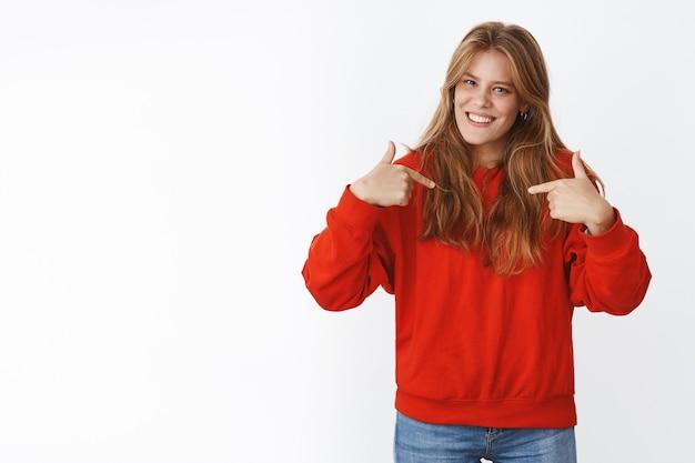 Fröhliche, sorglose, gut aussehende junge frau mit natürlichem blondem haar, sommersprossen und blauen augen, die in einem roten pullover steht und mit zufriedenem stolzem ausdruck auf sich selbst zeigt und mit ihren eigenen leistungen prahlt