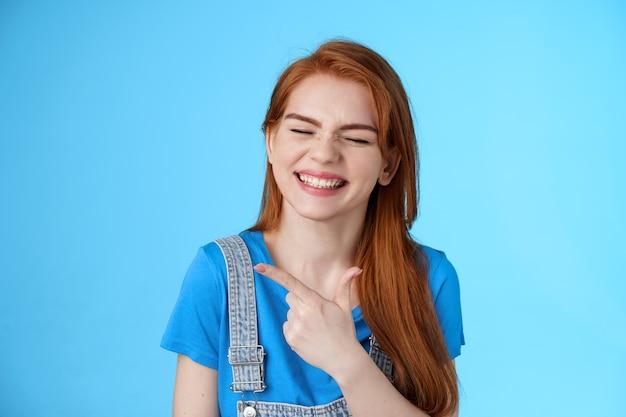 Fröhliche sorglose rothaarige frau aufrichtiges lächeln, nach links zeigend, kopieren sie den raum freudig, schließen sie die augen, zeigen sie weißes, zahniges grinsen erfreut, fühlen sie sich optimistisch, fröhliche positive stimmung, blauer hintergrund