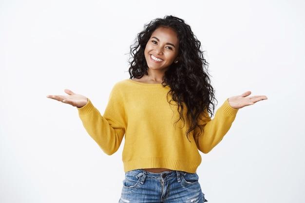 Fröhliche, sorglose, verführerische afroamerikanerin mit lockiger dunkler frisur im gelben pullover, die hände seitlich ausgebreitet, ungestört mit den schultern zucken und sorglos lächeln, jubeln hat keine mühe