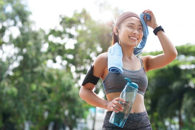 Fröhliche sportlerin mit flasche und handtuch