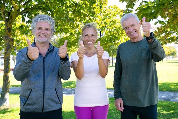 Fröhliche, sportliche, reife menschen, die nach den morgenübungen im park zusammenstehen, lächeln und daumen hoch zeigen. konzept für ruhestand oder aktiven lebensstil